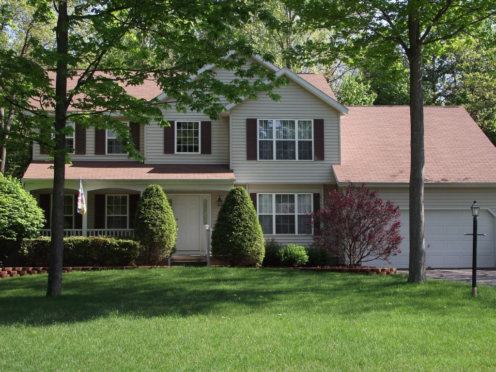 two story home with manicured lawn and nicely trimed trees and shrubs.
